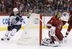 Phoenix Coyotes' Thomas Greiss (1), of Germany, gives up a goal to Winnipeg Jets' Andrew Ladd as Jets' Michael Frolik (67) skates behind the net during the first period Tuesday.
