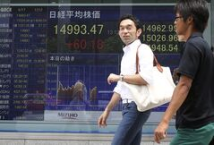 People walk by an electronic stock board of a securities firm in Tokyo, Tuesday, June 17, 2014. Asian stocks were mixed on Tuesday as investors remained cautious ahead of a meeting by the Federal Reserve that's expected to give an update on forecasts for the world's No. 1 economy. (AP Photo/Koji Sasahara)
