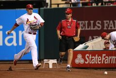 St. Louis Cardinals right fielder Allen Craig races a field usher to a fair ball off the bat of Philadelphia Phillies' Domonic Brown in sixth inning action during a game between the St. Louis Cardinals and the Philadelphia Phillies on Friday, June 20, 2014, at Busch Stadium in St. Louis. (AP Photo/St. Louis Post-Dispatch, Chris Lee)