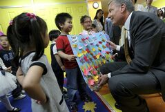 FILE - In this May 27, 2014 file photo, New York Mayor Bill de Blasio, right, visits children in a pre-kindergarten class at the Brooklyn Chinese American Association Early Childhood Education Center in the Brooklyn borough of New York. The rise in popularity of Brooklyn as a name for girls parallels the borough's renaissance. De Blasio, seeking to capitalize on the spirit of cool coursing through the city's most populous borough, last week pitched Brooklyn — not Manhattan — as a potential host for the 2016 Democratic National Convention. (AP Photo/Newsday, Linda Rosier, Pool, File)