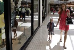 FILE - In this March 12, 2014, file photo, Anneka Johnson, of Estonia, walks with her son while shopping at Aventura Mall, in Aventura, Fla. The Commerce Department releases retail sales data for April on Tuesday, May 13, 2014. (AP Photo/Lynne Sladky, File)