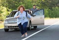 This undated publicity image released by Universal Pictures shows Jason Bateman, background, and Melissa McCarthy in a scene from,