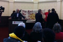 Protesters holding a banner stand behind Phil Fontaine Wednesday.