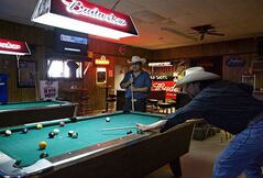 Ray Runnels, right, and his son Ray Runnels Jr. play a game of pool on Thursday, June 26, 2012, at Swett Tavern in Swett, S.D. The unicorporated town of Swett is owned by one person who has put it up for sale. (AP Photo/Rapid City Journal, Eric Ginnard) TV OUT