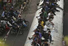 FILE - In this Jan. 17, 2012 file photo, people ride on the roofs of a commuter train in Jakarta, Indonesia. Indonesia has come up with another bizarre plan to keep commuters from riding on the roofs of trains: Swat them with brooms drenched in putrid goop.
