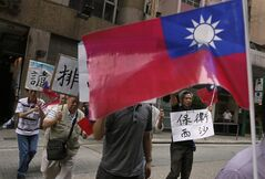 Protesters raise Taiwanese flags and placards marching to Vietnam's consulate in Hong Kong, Thursday, May 15, 2014, to protest anti-China unrest in Vietnam. Mobs burned and looted scores of foreign-owned factories in Vietnam following a large protest by workers against China's recent placement of an oil rig in disputed Southeast Asian waters, officials said Wednesday. The Chinese words in the photo read