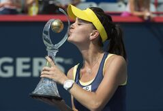 Agnieszka Radwanska of Poland kisses the winner's trophy after beating Venus Williams of the United States in the final at the Rogers Cup tennis tournament Sunday August 10, 2014 in Montreal. THE CANADIAN PRESS/Paul Chiasson