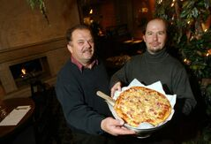 Papa George's owner Nick Kontzamanis, left, and evening manager Shane Ross display an always popular late-night dish.