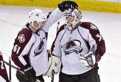 Colorado Avalanche's Andre Benoit (61) and goalie Jean-Sebastien Giguere (35) celebrate the win over the Edmonton Oilers during NHL hockey action in Edmonton, Alta., on Tuesday April 8, 2014. THE CANADIAN PRESS/Jason Franson