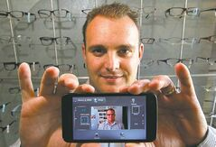 Sean Sylvestre of Eyewear Evolution holds a smartphone with his app for selling eyewear online.