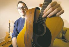Matt Weinstein holds an acoustic guitar he found abandoned in a West End back alley. It belonged to Bill Edmondson, who once played with Neil Young and local band The Squires.