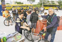 Bike valet Bill Newman takes care of fans' bikes as they arrive at Investors Group Field Thursday.