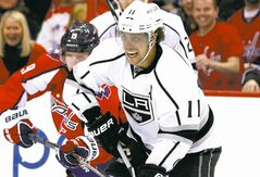Los Angeles Kings center Anze Kopitar (11), from Slovenia, skates with the puck with Washington Capitals center Nicklas Backstrom (19), from Sweden, behind him, in the first period of an NHL hockey game, Tuesday, March 25, 2014, in Washington. (AP Photo/Alex Brandon)