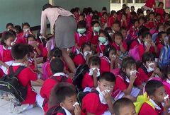 A teacher, left, helps her children to put on masks after a chemical leak from a ship near their school in Laem Chabang industrial seaport in Chonburi province, southeastern Thailand Thursday, July 17, 2014. More than 90 people, including primary school students, were sickened by a chemical leak from a Hong Kong ship in eastern Thailand on Thursday, authorities said. (AP Photo)