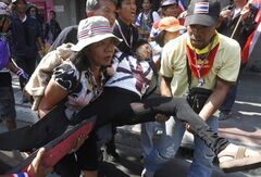 An anti-government protester injured in an explosion is carried by her fellow protesters during a demonstration in Bangkok, Thailand, Friday, Jan. 17, 2014. Dozens of people were wounded when an explosion hit anti-government demonstrators marching through Bangkok in some of the bloodiest violence reported this year. (AP Photo/Astv Manager Newspaper) THAILAND OUT