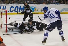 LA Kings' Jonathan Quick, LA Kings' Willie Mitchell and LA Kings' Drew Doughty, from left to right, try to reach the puck as Hamburg Freezers' Serge Aubin, foreground, scores his side's 3rd goal during their exhibition hockey match in Hamburg, Germany, Tuesday, Oct. 4, 2011. (AP Photo/Gero Breloer)