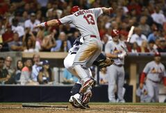 St. Louis Cardinals' Matt Carpenter attempts to avoid the tag by San Diego Padres catcher Rene Rivera while trying to score from third on an infield grounder by Matt Holliday in the fifth inning of a baseball game Tuesday, July 29, 2014, in San Diego. Carpenter was out on the play. (AP Photo/Lenny Ignelzi)