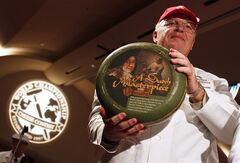 FILE - In this March 7, 2012, file photo Robert Aschenbrock of Stratford, Wis., shows off a low-fat gouda from the Netherlands, that won the 2012 World Champion Cheese Contest in Madison, Wis. The 24-pound wheel of cheese brought in $8,400, or $350 per pound, when it was auctioned off Wednesday, April 11, 2012. (AP Photo/Andy Manis, File)