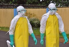Health workers wearing protective gear go to remove the body of a person who is believed to have died after contracting the Ebola virus in the city of Monrovia, Liberia, Saturday, Aug. 16, 2014. THE CANADIAN PRESS/AP, Abbas Dulleh