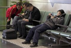 Men browse their tablet computers and smartphone at the Beijing Capital Airport in Beijing on Nov. 30, 2013. THE CANADIAN PRESS/AP, Andy Wong