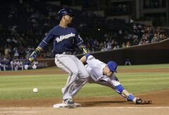 Milwaukee Brewers' Jean Segura, left, reaches first on a throwing error by Chicago Cubs second baseman Logan Watkins to first baseman Chris Valaika, during the ninth inning of a baseball game Wednesday, Sept. 3, 2014, in Chicago. The Cubs won 6-2. (AP Photo/Charles Rex Arbogast)