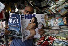 A man reads the December issue of FHM India, a popular Indian men's magazine that has a photograph of Pakistani actress Veena Malik on the cover at a way side stall in Mumbai, India, Monday, Dec. 5, 2011. Malik is suing FHM India for millions of dollars, accusing it of publishing photos she says were doctored to make her appear nude, her lawyer said Monday. (AP Photo/Rafiq Maqbool)