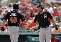 Miami Marlins' Garrett Jones, left, is congratulated by teammate Giancarlo Stanton after hitting a two-run home run during the first inning of an exhibition spring training baseball game against the St. Louis Cardinals Friday, Feb. 28, 2014, in Jupiter, Fla. (AP Photo/Jeff Roberson)
