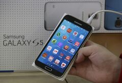 FILE - In this March 27, 2014 file photo, an employee shows Samsung's Galaxy S5 smartphone at a mobile phone shop in Seoul, South Korea. A California jury determined Friday May 2, 2014, that Samsung infringed Apple smartphone patents and awarded $120 million damages. (AP Photo/Lee Jin-man, File)