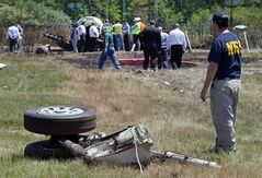 A National Transportation Safety Board official stands beside a piece of the landing gear at the scene Monday, June 2, 2014, in Bedford, Mass., where a plane plunged down an embankment and erupted in flames during a takeoff attempt at Hanscom Field on Saturday night. Lewis Katz, co-owner of The Philadelphia Inquirer, and six other people died in the crash. (AP Photo/Boston Herald, Mark Garfinkel, Pool)
