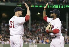 Boston Red Sox starting pitcher Jon Lester, left, congratulates center fielder Jackie Bradley Jr. after catching a fly out by Cleveland Indians Michael Bourn, and throwing out base runner Mike Aviles off first, to end the top of the seventh inning of a baseball game at Fenway Park in Boston, Thursday, June 12, 2014. (AP Photo/Charles Krupa)