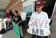 Ardian Zoto, right, an employee of Market Basket for six years, holds a sign outside the supermarket in Danvers, Mass., Monday, Aug. 4, 2014. Executives at the troubled Market Basket supermarket chain in New England say they have heard from employees who are