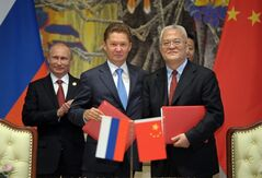 Russia's President Vladimir Putin, left, applauds, during signing ceremony in Shanghai, China on Wednesday, May 21, 2014 while Russian Gazprom CEO Alexei Miller, second left, and China's CNPC head Zhou Jiping, second right, hold documents, China's President Xi Jinping, stands partially seen at right. China signed a long-awaited, 30-year deal Wednesday to buy Russian natural gas worth some $400 billion in a financial and diplomatic boost to diplomatically isolated President Vladimir Putin. (AP Photo/RIA Novosti, Alexei Druzhinin, Presidential Press Service)