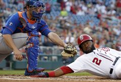 Washington Nationals' Denard Span is safe at home after the tag was late by New York Mets catcher Anthony Recker during the first inning of a baseball game at Nationals Park Friday, May 16, 2014, in Washington. (AP Photo/Alex Brandon)