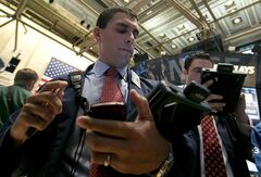 Trader Craig Spector, left, works on the floor of the New York Stock Exchange Wednesday, Aug. 6, 2014. U.S. stocks are little changed in early trading Wednesday as investors worry about escalating tensions between Russia and the Ukraine. Investors were also holding back after two larger merger bids were pulled. (AP Photo/Richard Drew)