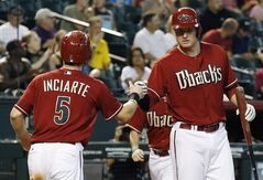Arizona Diamondbacks' Ender Inciarte (5) gets a fist-bump from teammate Mark Trumbo after scoring a run against the Colorado Rockies during the first inning of a baseball game Sunday, Aug. 31, 2014, in Phoenix. (AP Photo/Ross D. Franklin)