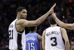 San Antonio Spurs' Tim Duncan (21) is congratulated by teammate Tony Parker after he scored against the Oklahoma City Thunder during the first half of Game 1 of a Western Conference finals NBA basketball playoff series, Monday, May 19, 2014, in San Antonio. (AP Photo/Eric Gay)