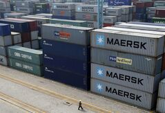 A worker walks past shipping containers piled at a port in Ningbo in east China's Zhejiang province, Tuesday, April 9, 2013. China reported higher import growth in March on Wednesday, April 10, 2013 in a possible positive sign for its economic recovery but analysts said doubts about the accuracy of Beijing's data made it hard to draw conclusions. (AP Photo) CHINA OUT