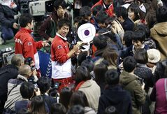 Kei Nishikori, center, of Japan signs autographs for fans after Japan's win over Canada at the 1st round of Davis Cup World Group tennis in Tokyo, Sunday, Feb. 2, 2014. (AP Photo/Shizuo Kambayashi)