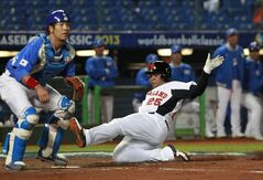The Netherlands' designated hitter Andruw Jones (25) slides into home plate to score a run under Korea's catcher Kang Minho (47) in the second inning of their World Baseball Classic first round game at the Intercontinental Baseball Stadium in Taichung, Taiwan, Saturday, March 2, 2013. THe Netherlands won 5-0. (AP Photo/Wally Santana)