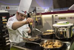 Alex Chen, of Canada, prepares food during the