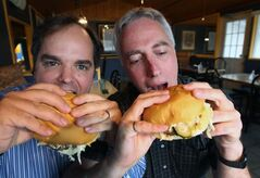 It's a tough job, but somebody's got to do it: Burger Club - Winnipeg members Scott Hewitt, left, and Tim Turner chow down on fatboys.