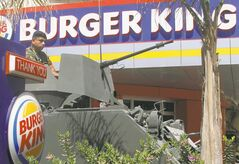 A Lebanese army soldier sits on his armored personnel carrier, as he stands guard outside the Burger King as part of stepped up security measures, in the southern port city of Sidon, Lebanon, Saturday.