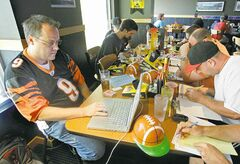 In this Aug. 30, 2010 photograph, Brian Sherman, left, uses his laptop to record moves in his team's fantasy football draft, at a Buffalo Wild Wings restaurant in Cincinnati. Some restaurant chains around the country have launched promotional drives to score with dedicated players of the growing pastime. (AP Photo/Al Behrman)