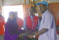 Ahmed Warsame presents the best-student award to a woman who graduated from the Red Cross's reproductive and preventive health care program at Ifo II refugee camp.