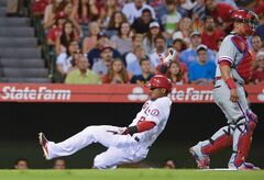Los Angeles Angels' Erick Aybar, left, scores on a sacrifice fly by Brennan Boesch as Philadelphia Phillies catcher Carlos Ruiz looks on during the second inning of a baseball game, Wednesday, Aug. 13, 2014, in Anaheim, Calif. (AP Photo/Mark J. Terrill)
