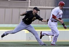 Pittsburgh Pirates shortstop Jordy Mercer (10) tags out Cincinnati Reds' Zack Cozart (2) after he was caught in a rundown in the first inning of a baseball game, Friday, July 11, 2014, in Cincinnati. (AP Photo/Al Behrman)