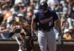 Minnesota Twins' Chris Parmelee (27) walks toward the dugout after striking out against the San Francisco Giants during the seventh inning of a baseball game in San Francisco, Sunday, May 25, 2014. The Giants won 8-1. Also pictured at left is Giants catcher Buster Posey. (AP Photo/Jeff Chiu)