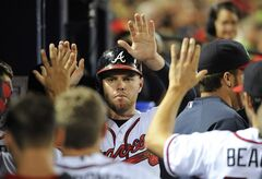 Atlanta Braves' Freddie Freeman, center, is greeted in the dugout after scoring against the San Diego Padres on a walk to Justin Upton during the eighth inning of a baseball game Friday, July 25, 2014, in Atlanta. The Padres won 5-2. (AP Photo/David Tulis)
