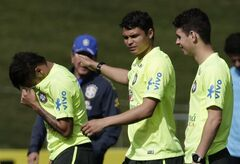 Brazil's Neymar, left, wipes tears after speaking with a special needs children as Thiago Silva pats him on the back during a practice session at the Granja Comary training center in Teresopolis, Brazil, Thursday, May 29, 2014. Brazil will host the World Cup soccer tournament that starts in June. (AP Photo/Hassan Ammar)