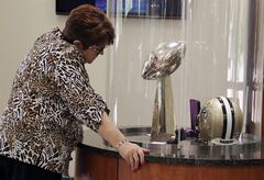 Vassie Owens, mother of New Orleans cheerleaer Kriste Lewis, looks at the Saints' Vince Lombardi trophy at the NFL football team's training facility in Metairie, La., Wednesday, July 16, 2014. Lewis is one of only two NFL cheerleaders in her 40s. (AP Photo/Bill Haber)
